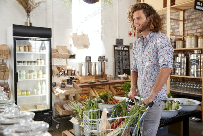 Young Man Buying Fresh Fruit And Vegetables In Sustainable Plastic Free Grocery Store