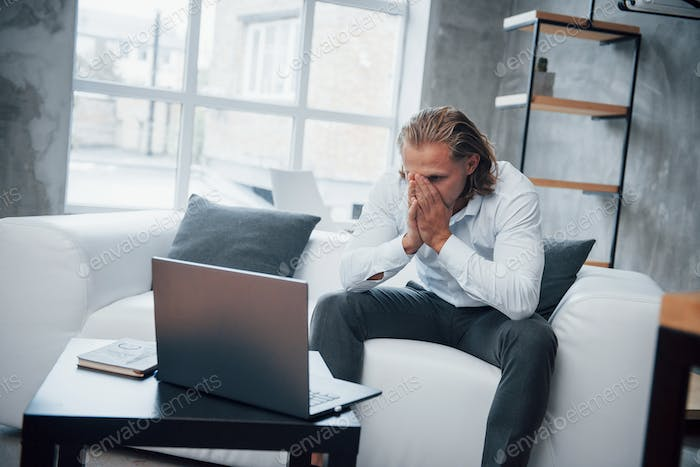 Looking at failure. Photo of young businessman sitting on coach and stressed out at work