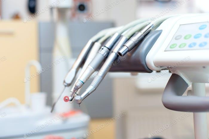 Dentalwerkzeuge auf Zahnarztstuhl mit medizinischer Ausrüstung und neuer Technologie
