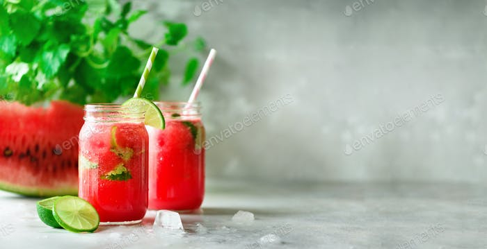Fresh red watermelon slice and smoothie in glass jar with straw, ice, mint, lime on light background