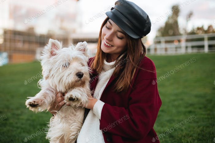 Beautiful lady in black cap and coat holding in hands her small cute dog while spending time in park