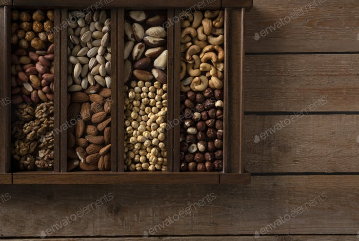 Wooden box with nuts on the left side of a wooden table