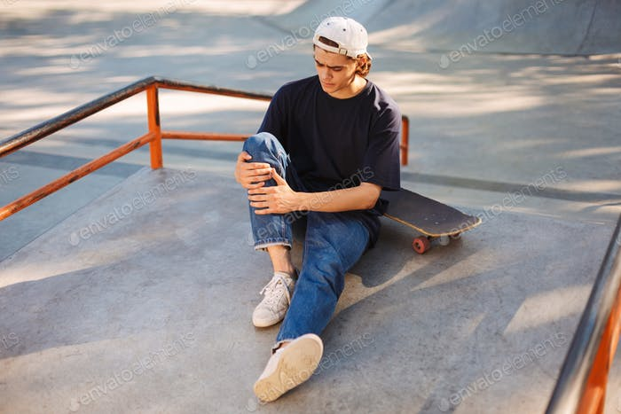 Young skater in cap holding his painful leg with skateboard near