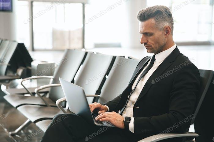Confident businessman using laptop computer