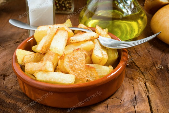 earthenware dish full of chips, with fork, salt and oil