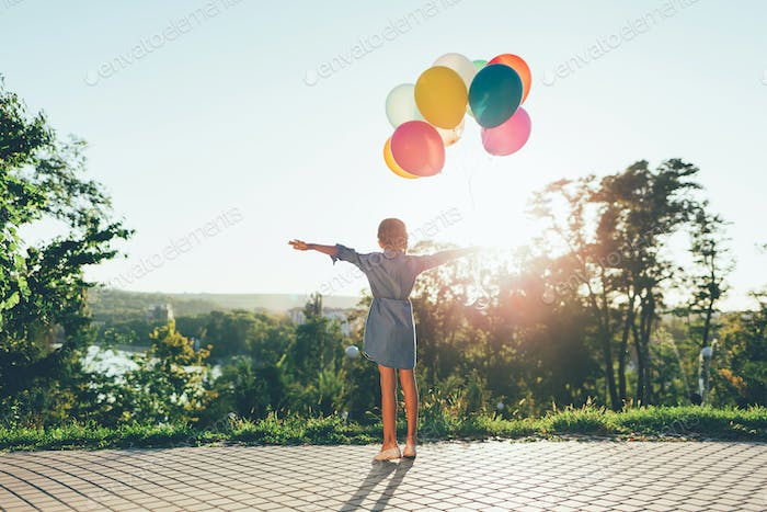 Cute girl holding colorful balloons in the city park spreding ar