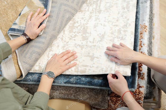 Hands of young female client and designer touching sample of floor covering