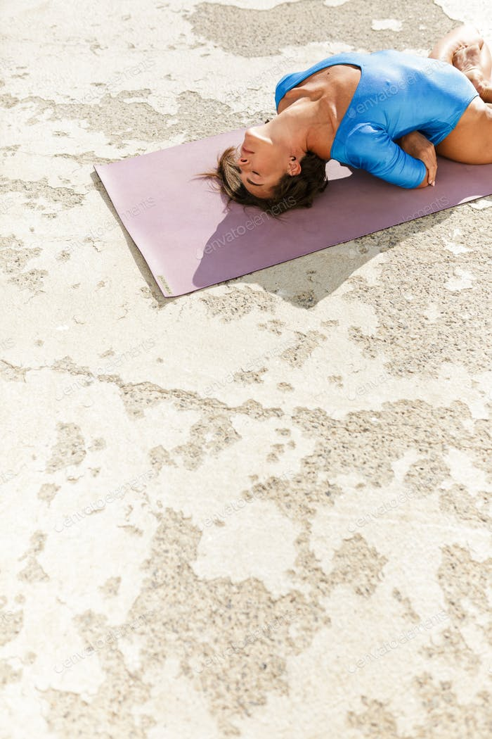 Young woman with dark sort hair lying on yoga mat and doing yoga while closing her eyes