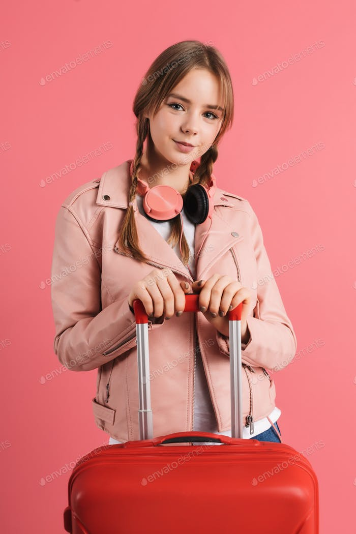 Cute teenager girl in leather jacket with headphones holding suitcase happily looking in camera