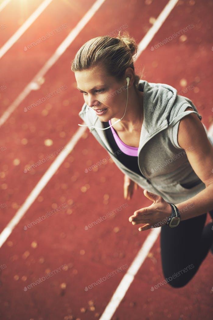 Nahaufnahme der sportlichen jungen Frau läuft schnell auf Stadion