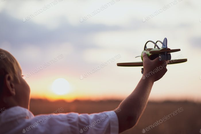 Happy child playing with a toy plane in nature during summer sunset.