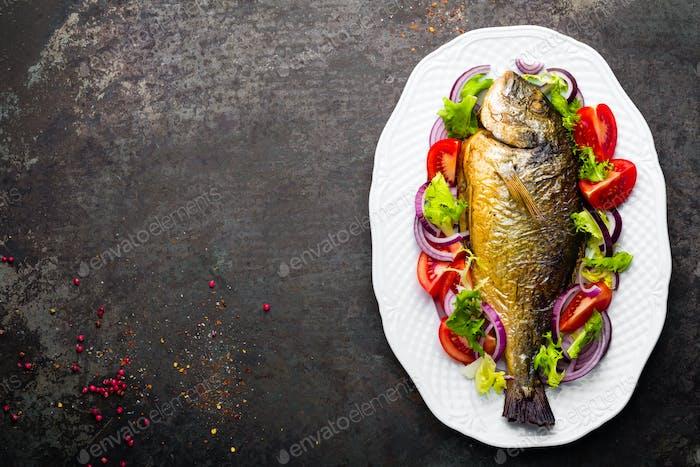 Baked fish dorado. Dorado fish oven baked and fresh vegetable salad on plate. Sea bream