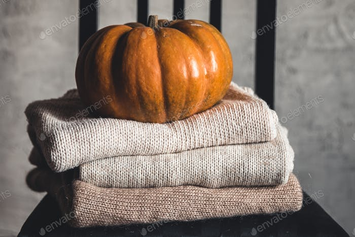 A stack of warm knitted sweaters on a white background. Autumn concept