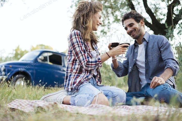 paar Verkostung Wein während eines Picknicks auf dem Land