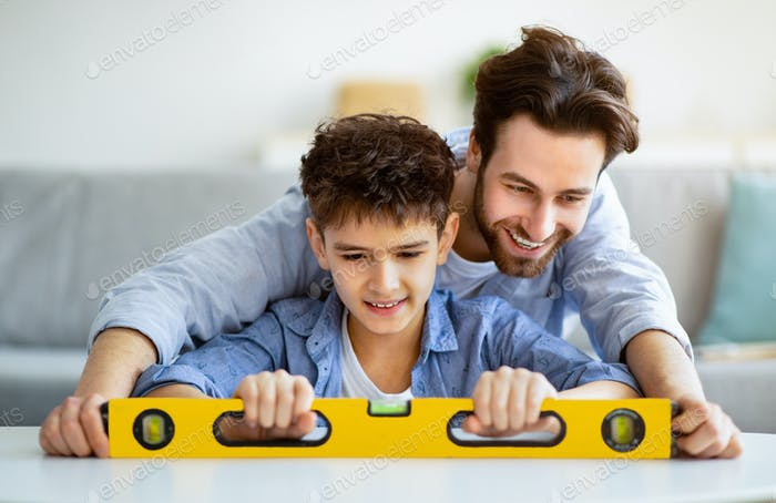 Happy father teach son using level tool for measure surface, doing apartment repair together