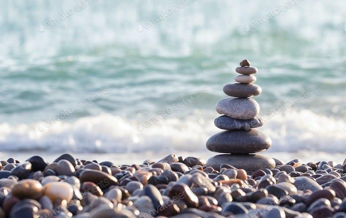 Pyramid of sea stones on pebbles of the sea shore