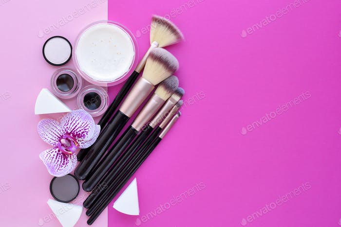 Makeup brush and decorative cosmetics and a orchid flower on pin