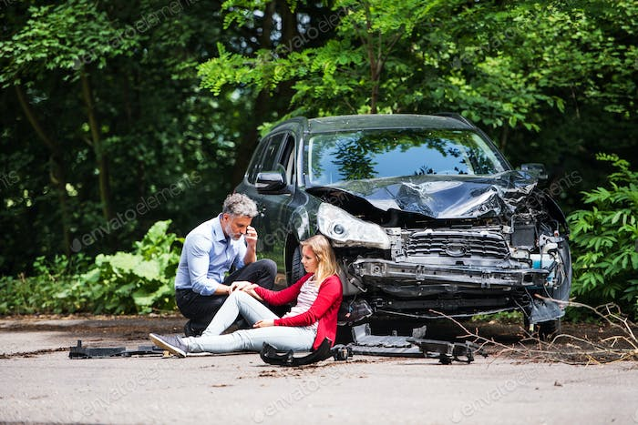 Young woman by the car after an accident and a man making a phone call.