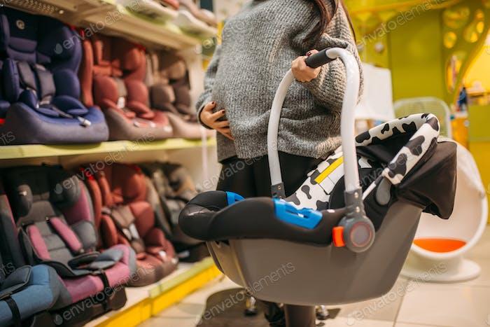 Mujer embarazada con cama portátil en tienda