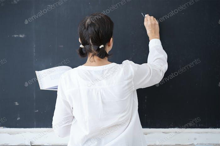 Teacher writing on blackboard in the classroom