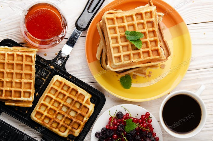 Flat lay view at Belgian Waffles on cast skillet and stacked on plate with syrup