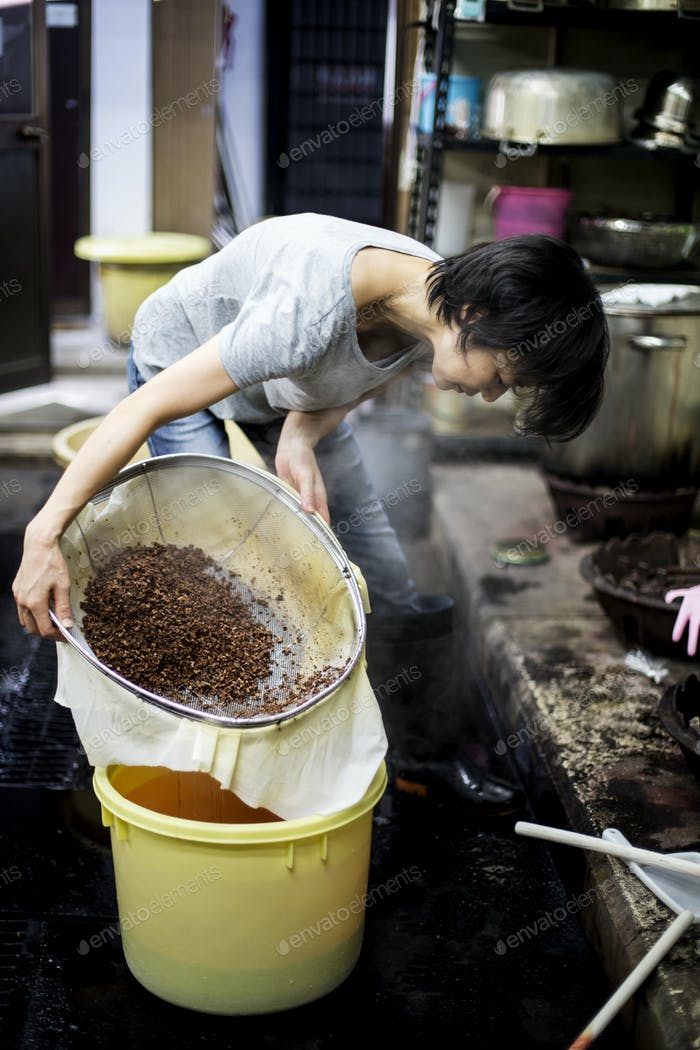 Japanese woman standing in a textile plant dye workshop, pouring plant dye from a sieve into a