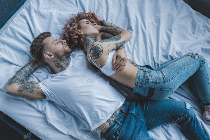 Top View of Tattooed Couple Hugging and Lying on Bed in Bedroom