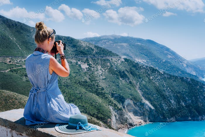 Adult female tourist with camera enjoying seascape of Kefalonia, Greece on summer holiday vacation