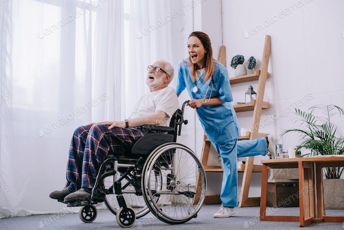Nurse and senior patient in wheelchair having fun