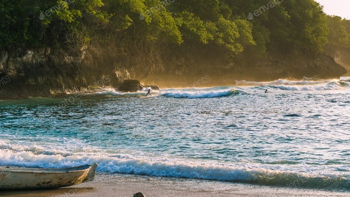 Niños locales surf en las olas en la luz del atardecer, hermosa bahía de cristal, Nusa Penida Bali