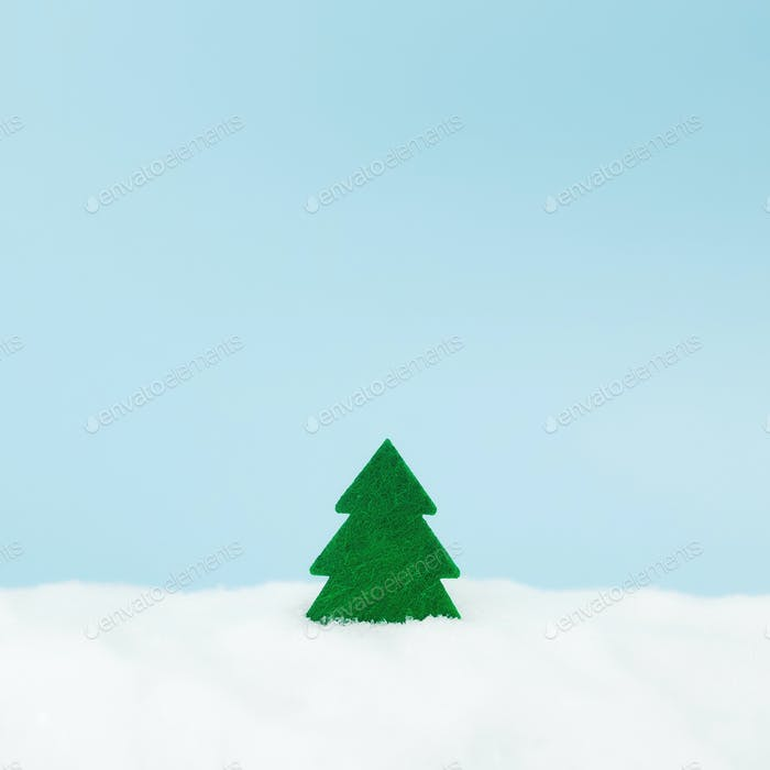 Green christmas tree on blue background with fake snow