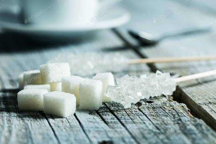 Kristallisierter Zucker auf Holzstab und Zuckerwürfel.