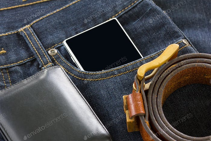 Wallet and smartphone on denim jeans