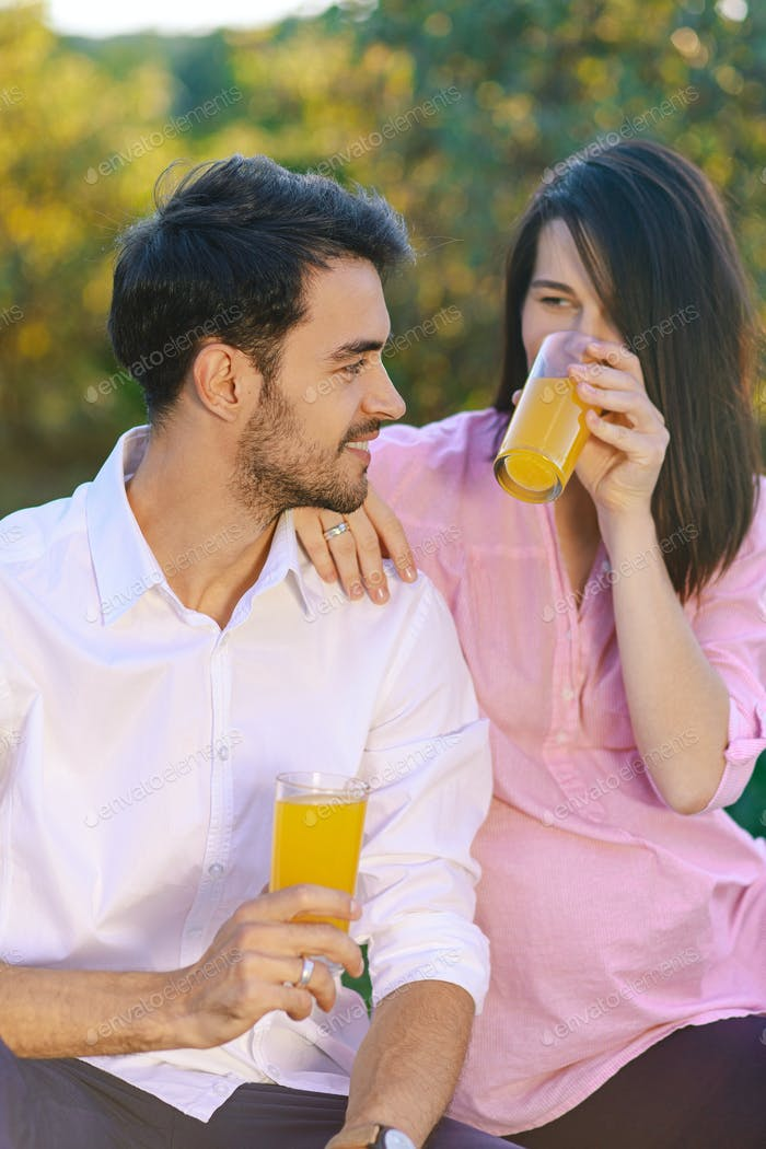 Happy couple drinking orange juice in the park looking to each o
