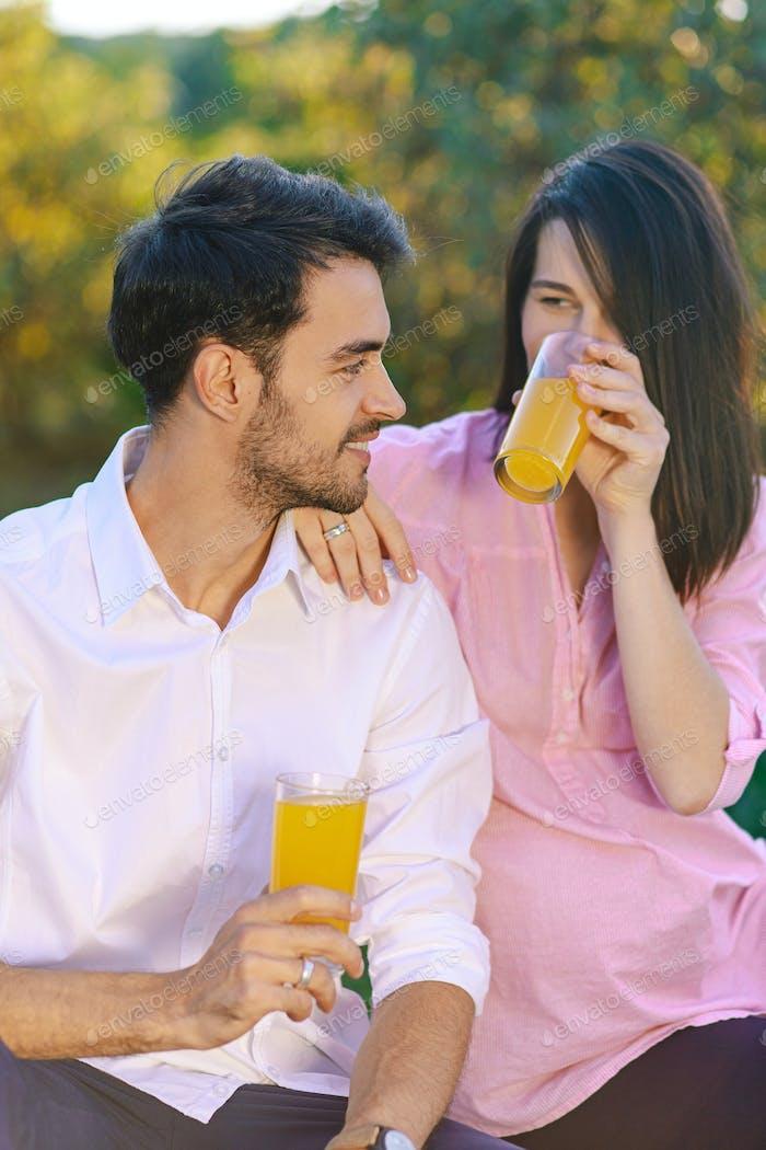 Glückliches Paar trinken Orangensaft im Park auf der Suche nach jedem o