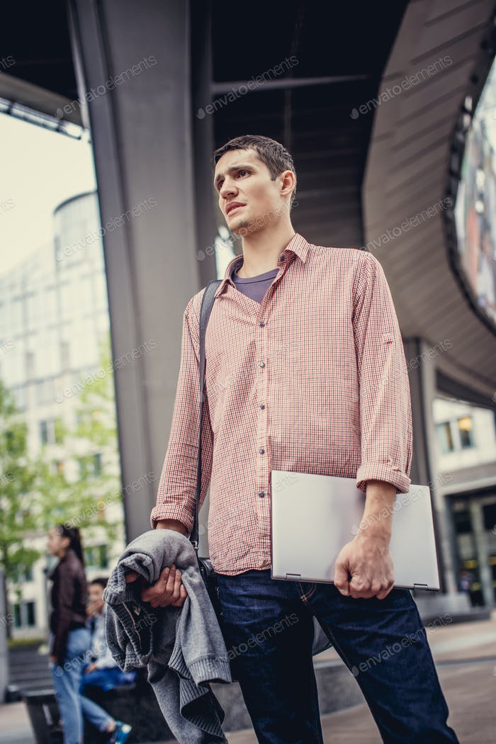 Man in casual clothes holding laptop