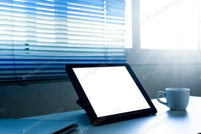 Blank screen tablet computer and a cup of coffee on the table