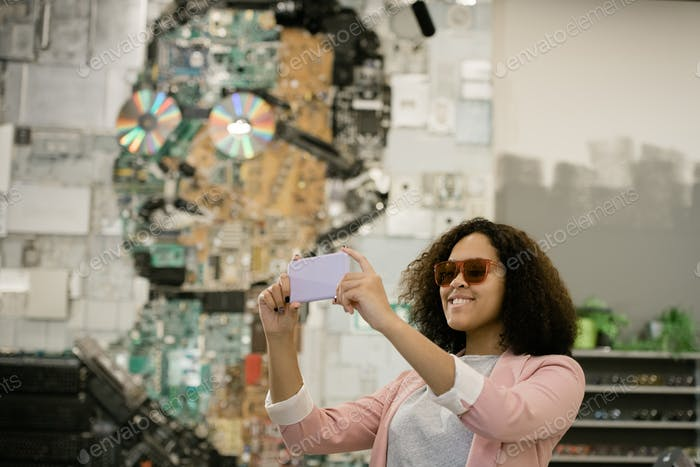 Young cheerful female in sunglasses making selfie in contemporary optics shop