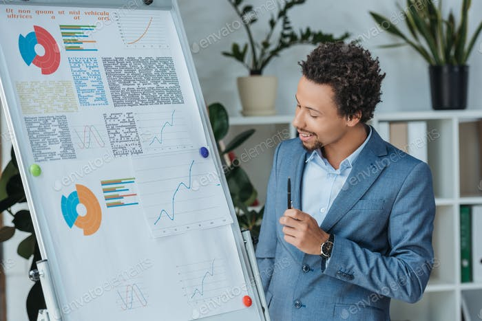 positive african american businessman looking at flipchart with infographics