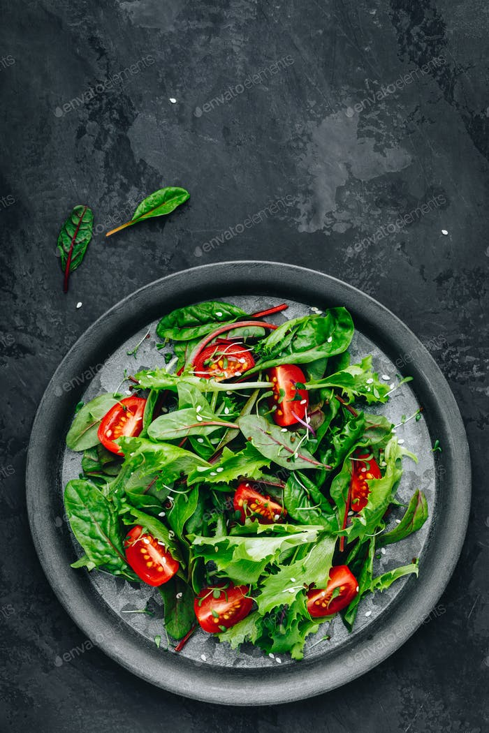 Fresh green mixed lettuce salad bowl with tomato, microgreen and sesame seeds