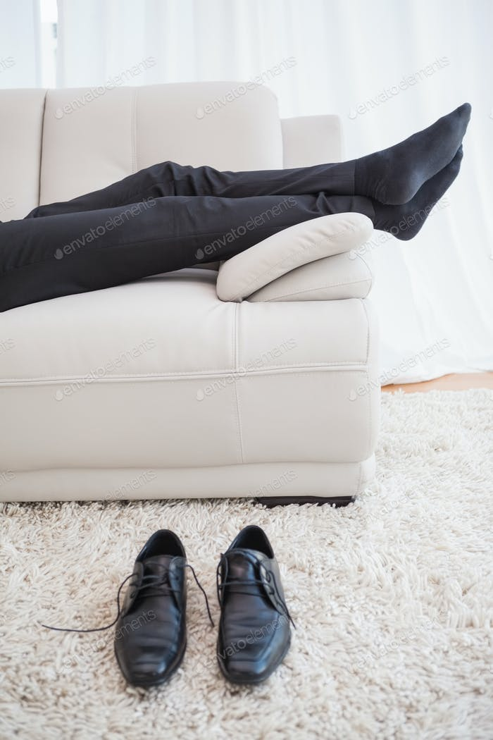 Businessman lying on couch legs only visible at home in the living room