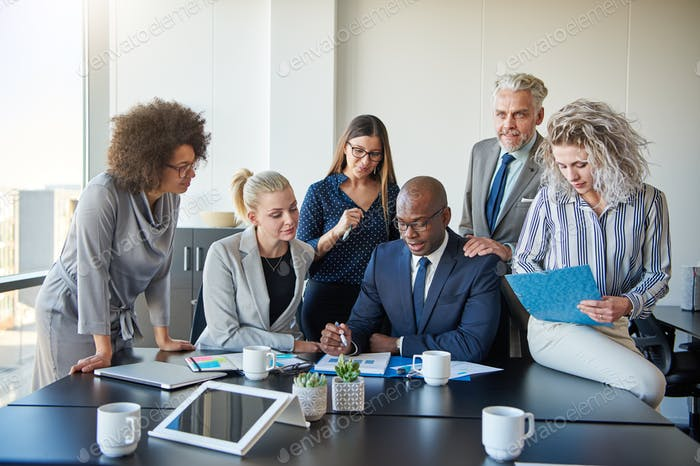 Diverse group of colleagues discussing paperwork together in an office