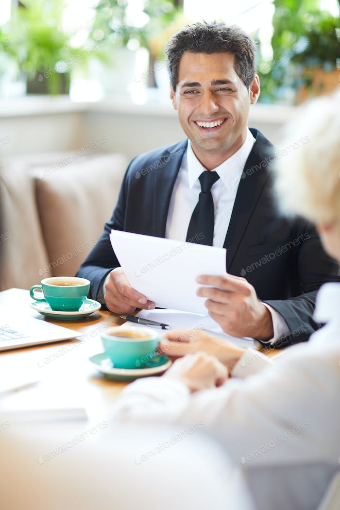 Cheerful lawyer talking to client in cafe