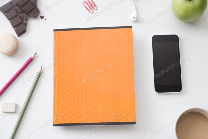 Top view of a working desk with orange notebook