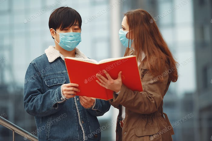A Chinese and European woman are wearing respirators