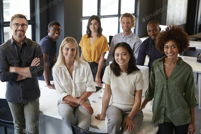 Portrait of a creative business team leaning on a desk, smiling to camera in office, elevated view