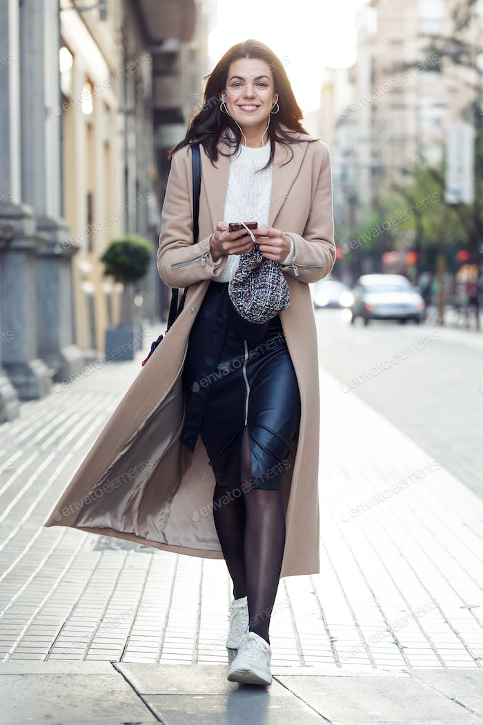 Pretty young woman looking at camera while listening to music with her mobile phone in the street.