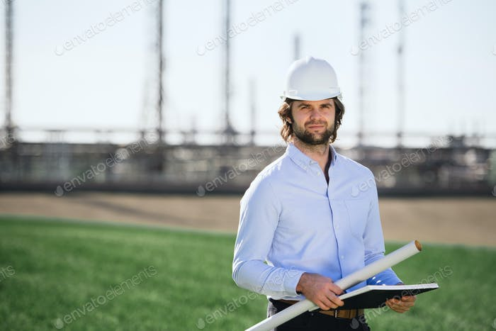 Young engineer with hard hat standing outdoors by oil refinery