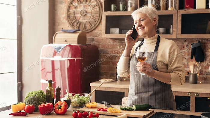 Cheerful senior woman enjoying glass of wine in kitchen