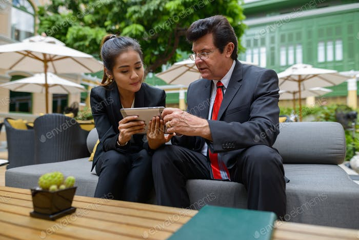 Mature businessman and young Asian businesswoman using digital tablet together
